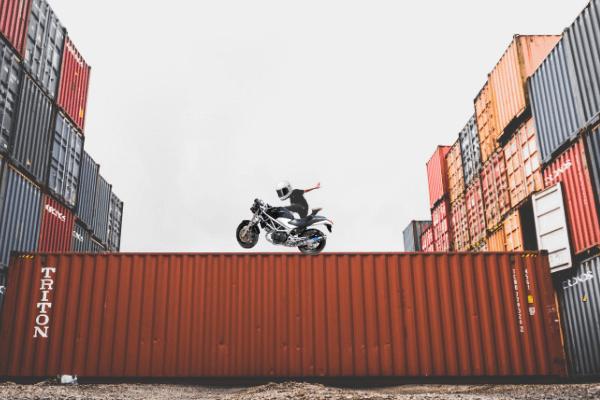 コンテナの上でバイクに乗る人