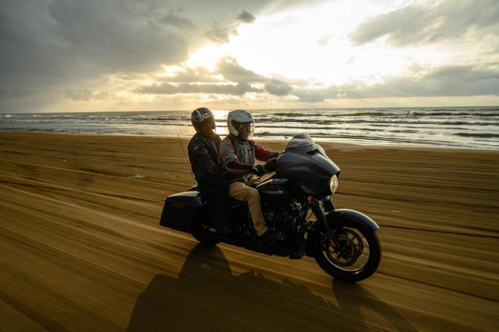 海岸を二人乗りで走るバイク
